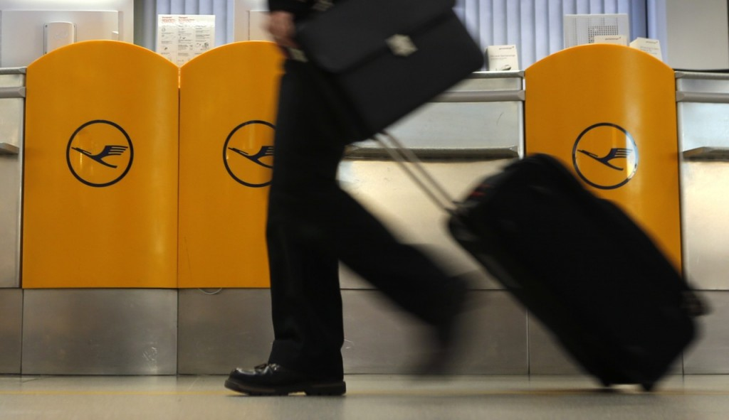 A passenger walks past a ticket counter of German air carrier Lufthansa at Berlin Tegel airport April 2, 2014. The union for Lufthansa pilots, Vereinigung Cockpit, called a strike for its members to demand higher wages and the airline had to cancel more than 3,800 flights. REUTERS/Fabrizio Bensch (GERMANY - Tags: TRANSPORT BUSINESS EMPLOYMENT SOCIETY)