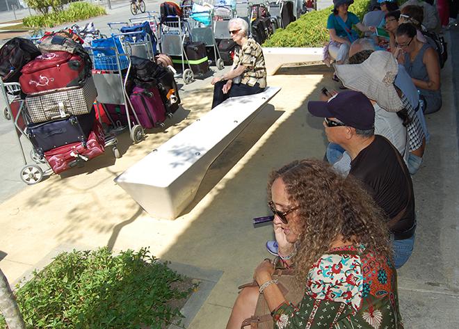 Turistas aguardam na rua a chamada para embarque