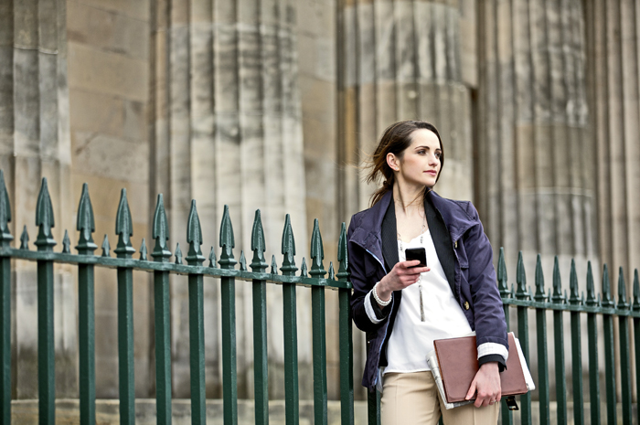 Modern Caucasian Business woman, talking on mobile smart phone outside. Beautiful young professional European businesswoman. Caucasian ethnicity.