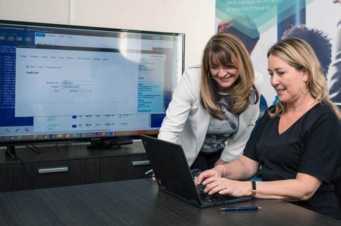 Claire Osborne na Travelport, com Kelly Doherty, da Meon Valley Travel, realizando a primeira transação por NDC no escritório da agência em Leicester, na Inglaterra. (Foto: PRNewswire)