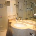 Banheiro conta com peça de mármore, banheira e amenities exclusivos da classe Yacht Club