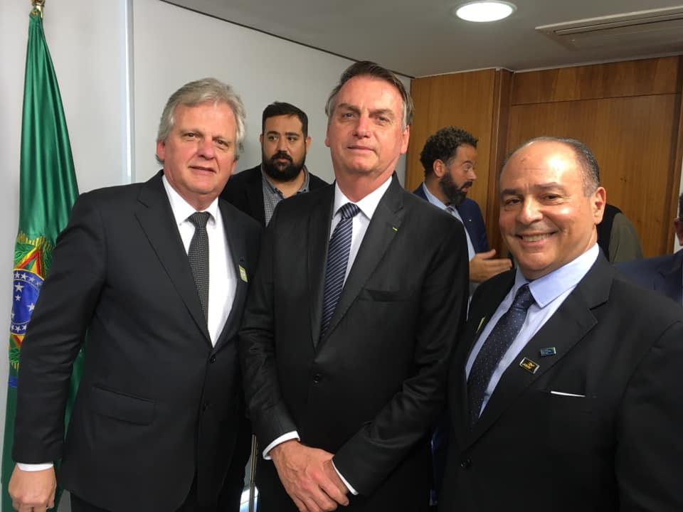 O presidente Jair Bolsonaro entre Edmar Bull e Geraldo Rocha, da Abav Nacional