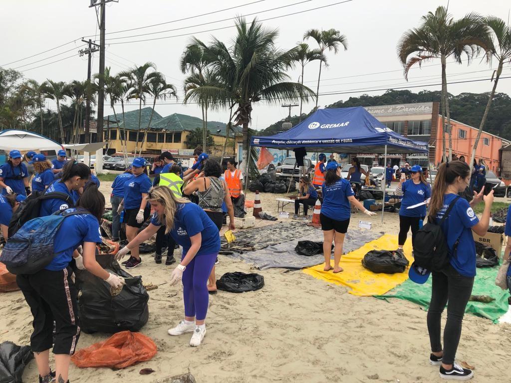 Agentes de viagens durante limpeza da praia no litoral de São Paulo