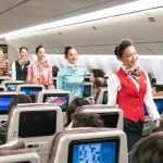 As comissárias de bordo, que vestiam uniformes vintage, andaram pelo corredor do voo como um desfile de moda