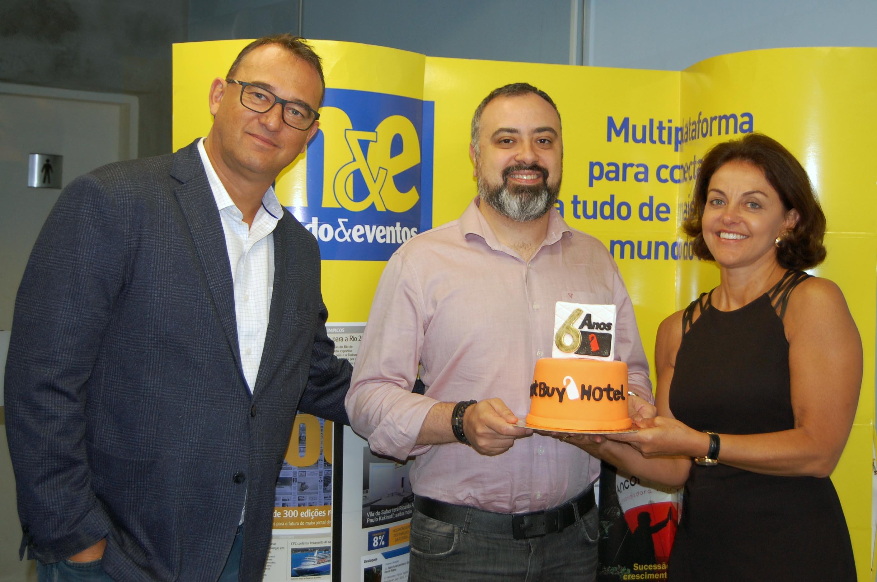 Anderson Masetto, do M&E, recebe o bolo de comemoração de seis anos da Best Buy, de Victor e Nice van Oorchot, CEO e diretora de Operações da operadora