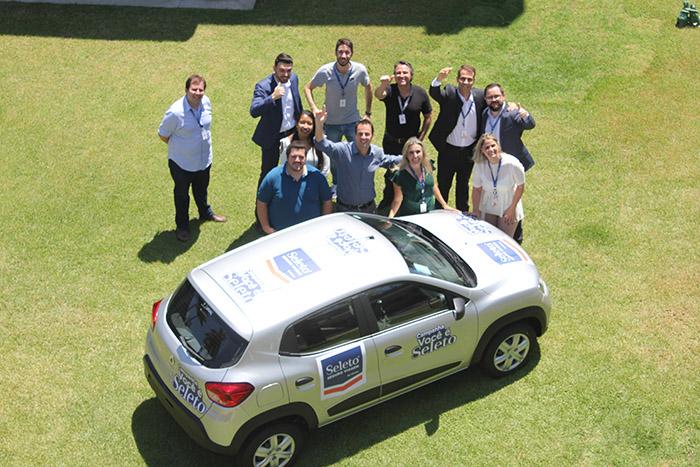 Equipe da Flytour ao lado do carro que será entregue ao agente de viagens vencedor da campanha