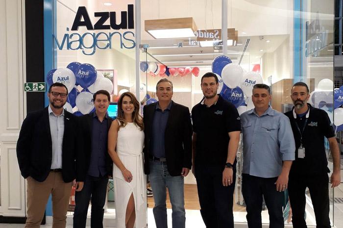 Daniel Bicudo (segundo, da esquerda para direita), diretor da Azul Viagens, e Alessandra Perez (vestido branco), proprietária da nova loja da Azul Viagens, celebram juntos com Tripulantes da operadora de turismo a expansão da unidade de negócios da Azul