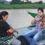 Durante o passeio do pôr do sol, músicos tocam ao vivo em pequenos botes ao entardecer