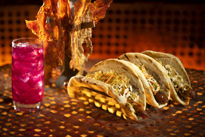 Guests will discover innovative and creative eats from around the galaxy at Star Wars: Galaxy's Edge at Disneyland Park in Anaheim, California and at Disney's Hollywood Studios in Lake Buena Vista, Florida. Pictured here, left to right, are the Meiloorun Juice, the Nuna Turkey Jerky and the Ronto Wrap filled with roasted pork, grilled sausage, peppercorn sauce and tangy slaw wrapped in pita found at Ronto Roasters, located in the Black Spire Outpost market. (Kent Phillips/Disney Parks)