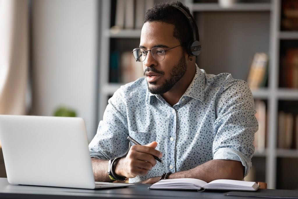 Focused african businessman wear headphones study online watching webinar