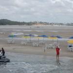Turistas e visitantes passeiam pelo banco de areia onde pode consumir bebidas