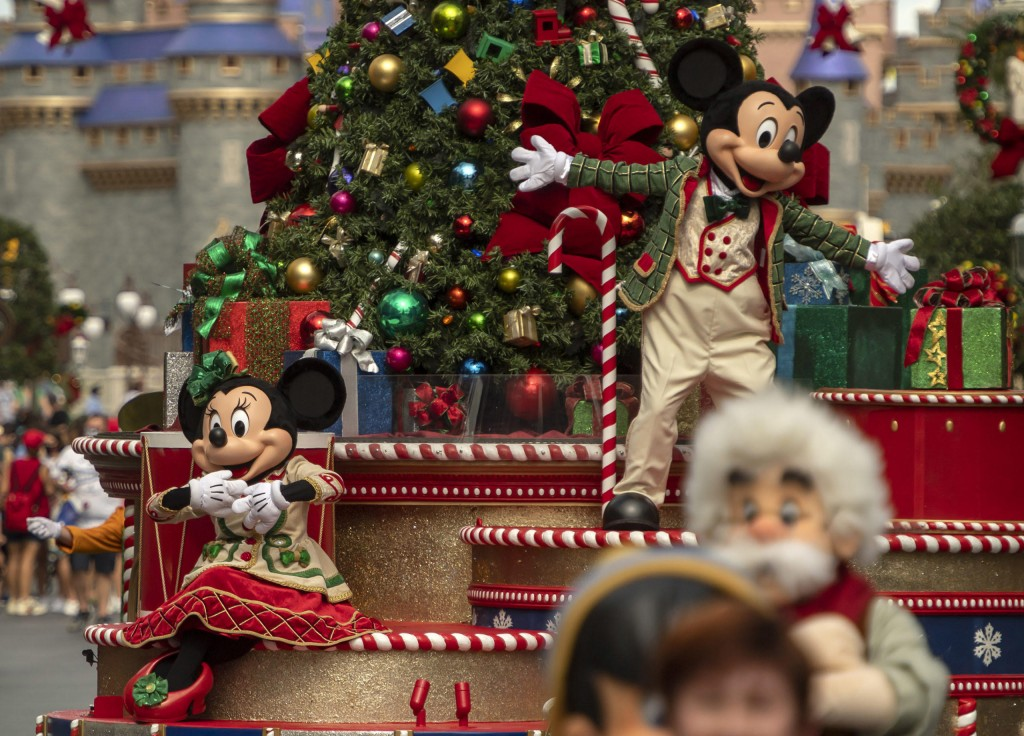 Minnie Mouse (left) and Mickey Mouse (right) wave to guests during their cavalcade down Main Street, U.S.A., as part of the holiday celebrations at Magic Kingdom Park at Walt Disney World Resort in Lake Buena Vista, Fla. (Kent Phillips, photographer)