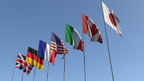 Seven flags of the Group of Seven are developing against the blue sky. G7