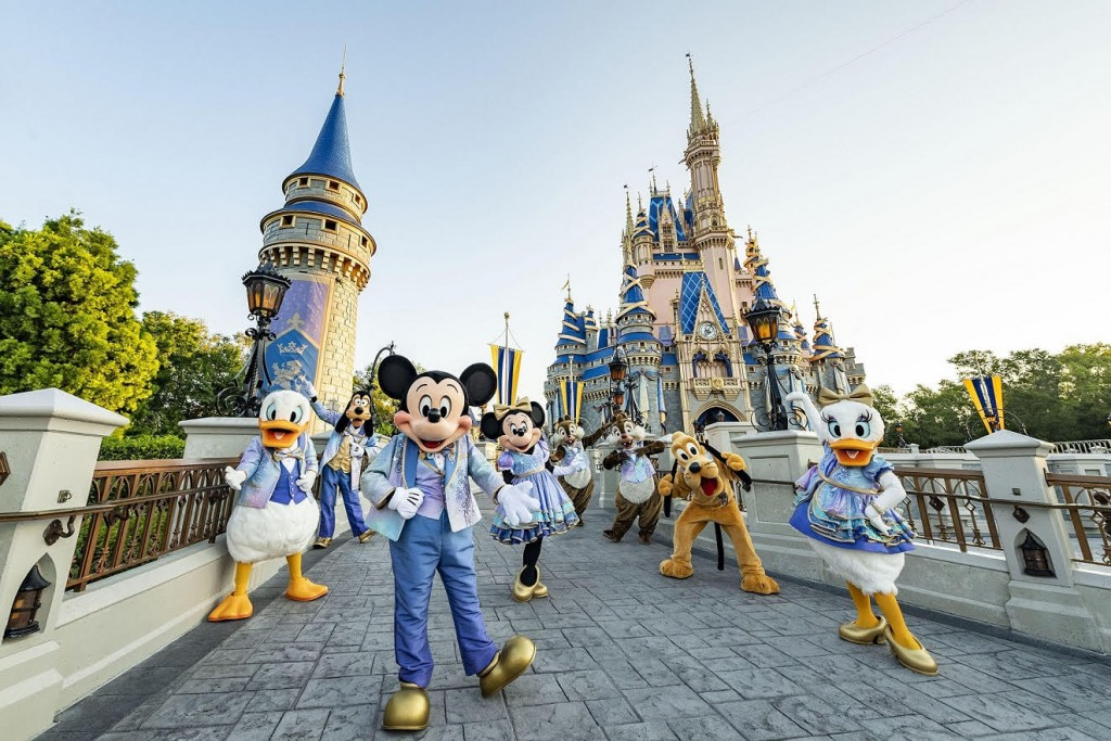 """Beginning Oct. 1, 2021, Mickey Mouse and Minnie Mouse will host """"The World's Most Magical Celebration"""" honoring the 50th anniversary of Walt Disney World Resort in Lake Buena Vista, Fla. Mickey and Minnie will be joined by their best pals Donald Duck, Daisy Duck, Goofy, Pluto and Chip 'n' Dale all dressed in sparkling new looks, custom-made for the 18-month event, highlighted by embroidered impressions of Cinderella Castle on multi-toned, EARidescent fabric punctuated with pops of gold. (Matt Stroshane, photographer)"""