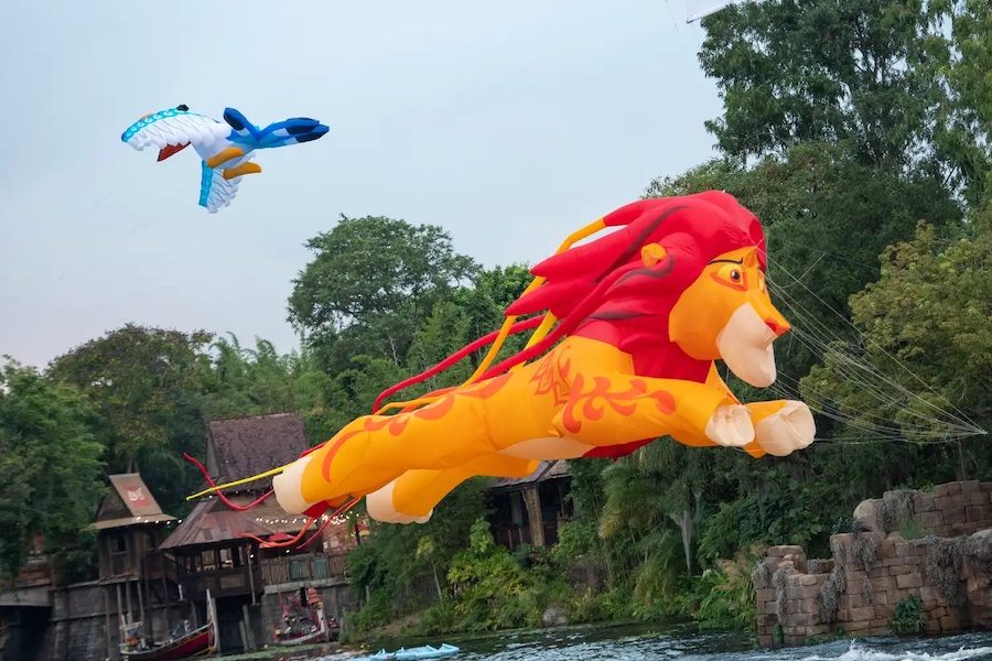 """New daytime entertainment is stirring at Disney's Animal Kingdom Theme Park, as """"Disney KiteTails"""" comes alive several times daily beginning Oct. 1, 2021, at Walt Disney World Resort in Lake Buena Vista, Fla. Performers fly windcatchers and kites of all shapes and sizes, while out on the water elaborate three-dimensional kites – some stretching to 30 feet long – depict Disney animal friends, including Simba, Zazu, Baloo and King Louie. These colorful creations dance through the sky to the beat of favorite Disney songs in an uplifting, vibrant experience for the whole family. (David Roark, photographer)"""