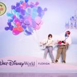 Karol Pinheiro e Maqui Nóbrega seguram os balões da Disney com o Castelo da Cinderela ao fundo