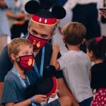 Pai e filho curtem o evento com chapéu e máscara do Mickey
